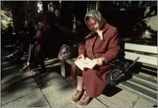 Elderly Woman Sitting on Bench Reading Book